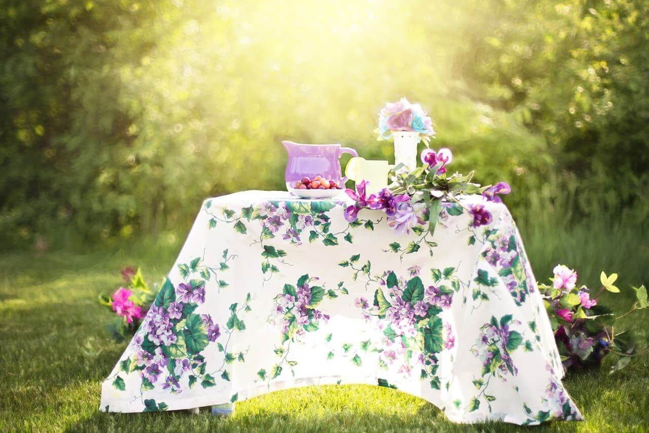 garden table covered with a very flowery tablecloth with a glass of lemonade, a pitcher and a bouquet of flowers on top.