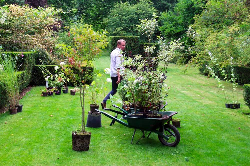 Guillaume, our landscaper, at work, surrounded by plants ready to be planted.