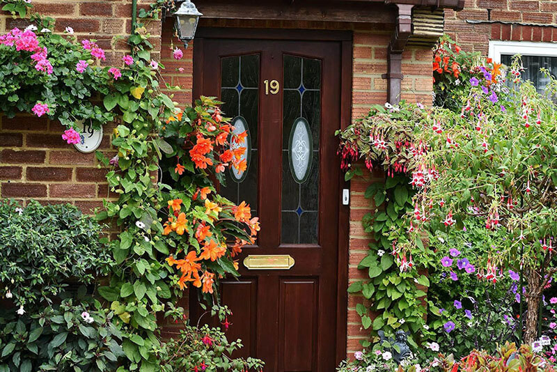 Front of an English house with a very flowery and colourful garden